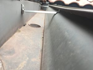 Scooping debris out of gutters